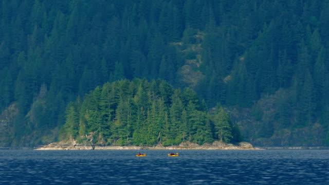 People Canoe Near Small Island In Rugged Landscape video
