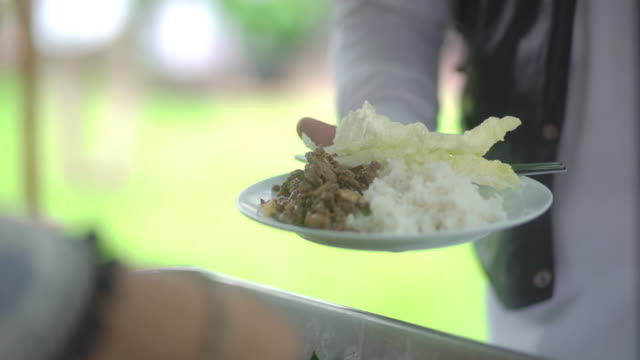 People carrying a plate with meat dish on a buffet food table at the dinner party