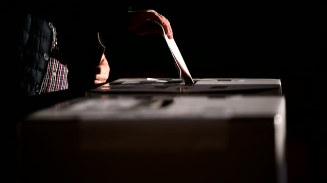 People casting votes into the ballot box
