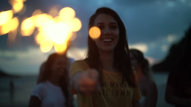 stockvideo's en b-roll-footage met mensen vieren het nieuwe jaar op het strand met sparkler - 25 29 jaar