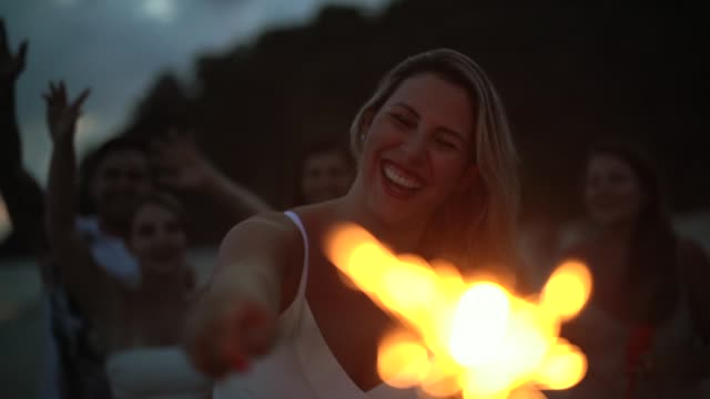 people celebrating the new year on the beach with sparkler - giorno dell'indipendenza video stock e b–roll