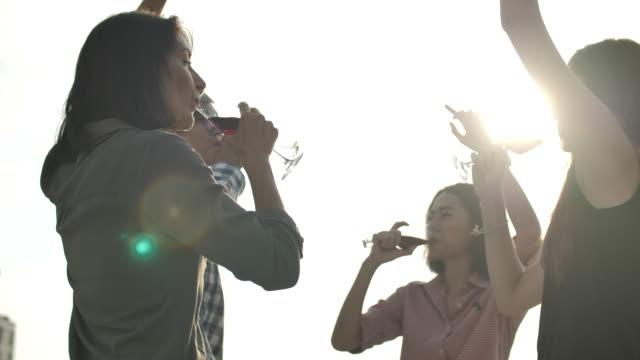 vidéos et rushes de célébration de personnes ayant l'amusement et buvant le vin à la partie de toit - man drinking terrace