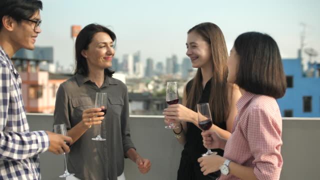 çatı partisi 'nde şarap ile insanlar kutlama - bar i̇çkili mekan stok videoları ve detay görüntü çekimi