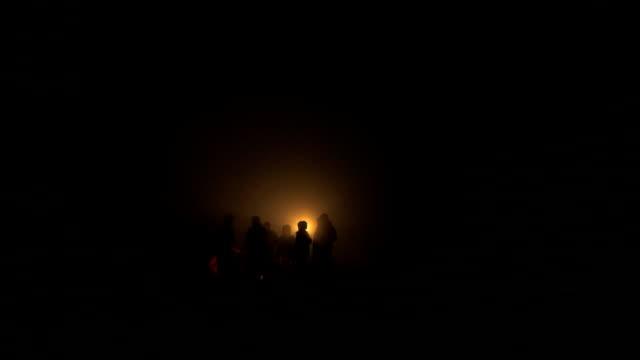 People chatting around Campfire on misty night video