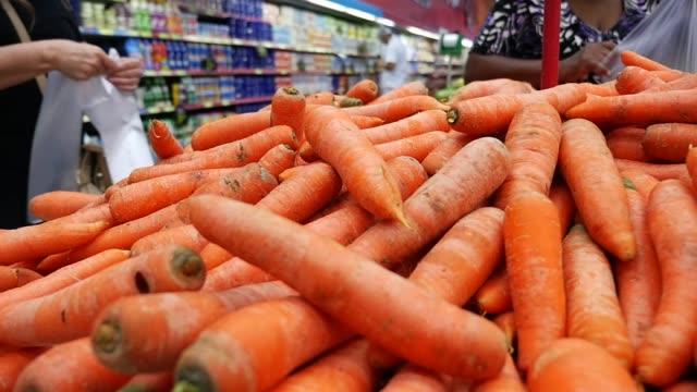 människor som väljer grönsaker i snabbköpet - morot bildbanksvideor och videomaterial från bakom kulisserna