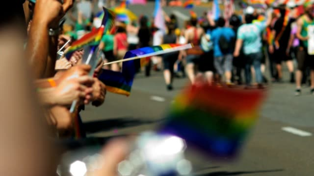 People clap, cheer and hold wave rainbow flags as gay pride parade marchers walk