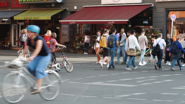 People cross the street and some people ride bicycles in Berlin, Germany Busy road junction and Subway Station Eberswalder Strasse in Berlin Prenzlauer Berg, pedestrian crossing street. cycle vehicle stock videos & royalty-free footage