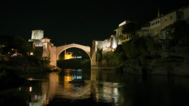 夜にモスタルの古い橋を渡るwaの人々 - ボスニア・ヘルツェゴビナ点の映像素材/bロール