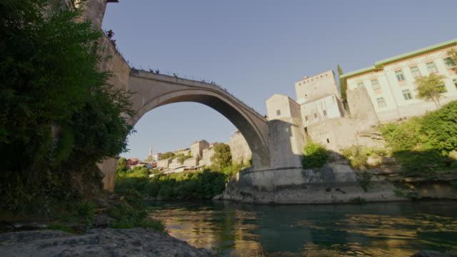 モスタルのネレトヴァ川に架かる古い橋を渡るlaの人々 - ボスニア・ヘルツェゴビナ点の映像素材/bロール