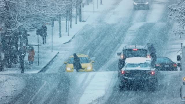 People Crossing Busy Road In Snowstorm