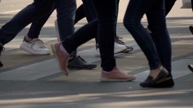 stockvideo's en b-roll-footage met mensen kruising zebrapad in de stad. benen van menigte mensen lopen op het zebrapad. slow motion - oversteekplaats