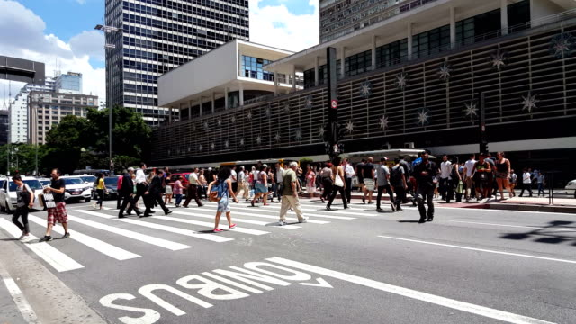 People crossing Paulista Avenue People crossing the Paulista Avenue, located at Sao Paulo city. Pedestrian crossing the most importante avenue of the city. são paulo state stock videos & royalty-free footage