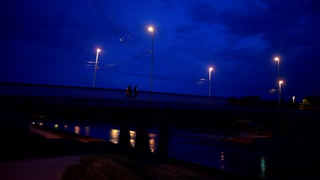 夜明けに橋を渡る人々 - 街灯点の映像素材/bロール