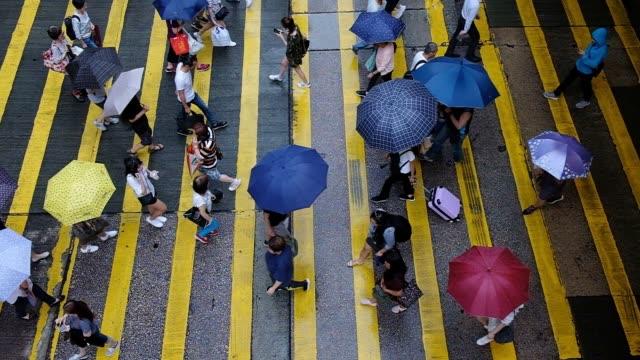 vídeos de stock e filmes b-roll de people crossing the road - guarda chuva