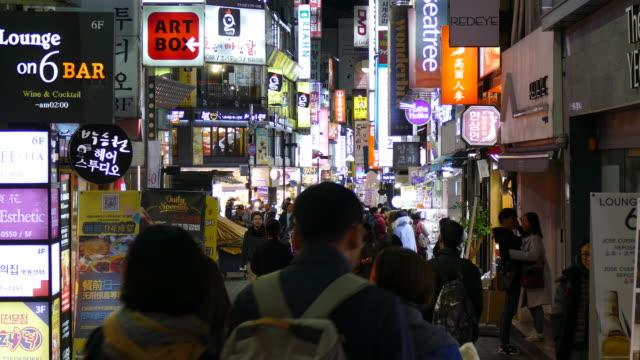 vídeos de stock, filmes e b-roll de pessoas lotadas no mercado de rua de myeongdong - coreia