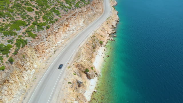 AERIAL: People cruising along the stunning shoreline of Lefkada in a grey car. AERIAL: People cruising along the stunning shoreline of Lefkada in a grey car and observing the tranquil deep blue sea. Flying behind a car driving along the coastline of an island in Mediterranean. greek islands stock videos & royalty-free footage