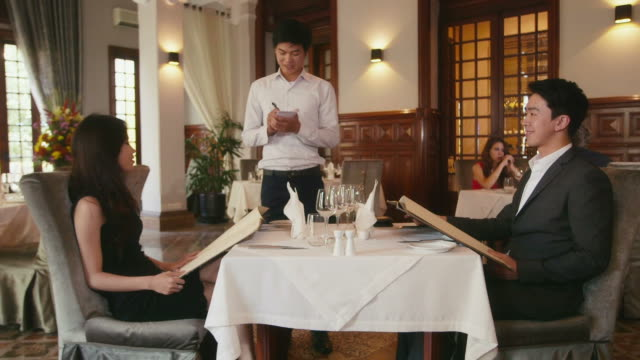 People dining in hotel restaurant, husband, wife, waiter People dining at restaurant, lifestyle in resort, man and woman on honeymoon, husband and wife celebrating anniversary, talking to server with wine list. 22of26 menu stock videos & royalty-free footage