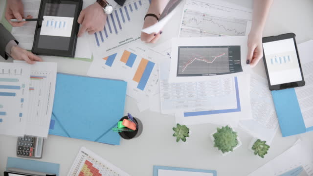 cs people discussing charts on the table at the meeting - scrivania video stock e b–roll