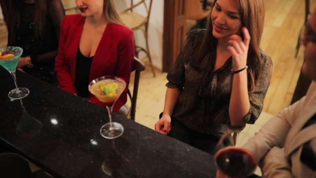 People drinking cocktails at the bar