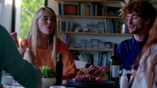 飲んで、食べて、話してを人々 します。4 人の白人の友人男女地中海イタリアン サラダ、肉のハンバーグとパンのランチやディナー。現代住宅 4 k ハンドヘルド ビデオで自宅で夏パーティー ビデオ