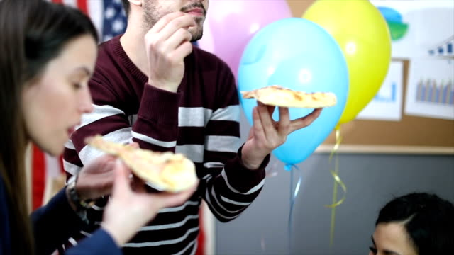 People eating pizza on a birthday party video
