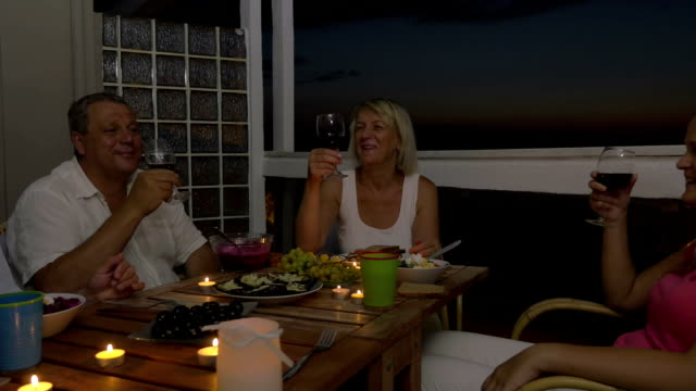 People enjoying food and wine during home dinner video