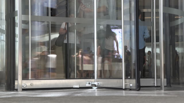 people entering and exiting through revolving doors - hotel reception filmów i materiałów b-roll