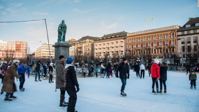 personer som utövar skridskoåkning på utomhus isbanor runt statyn, beläget i stockholm, sverige - stockholm bildbanksvideor och videomaterial från bakom kulisserna