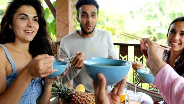 Personas alimentadas mutuamente con deliciosos fideos asiáticos alimentos, grupo de amigos sentarse en la mesa en terraza vista en Bosque Tropical - vídeo