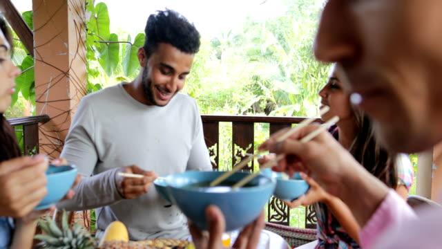 Menschen ernähren einander mit Delicious Nudeln asiatisch Essen, Freunde Gruppe sitzen am Tisch auf der Terrasse mit Blick auf Wälder – Video