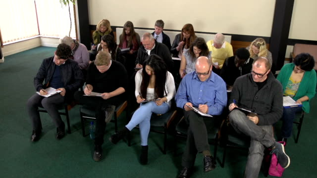 People filling out forms / questionaires : HD Crane Stock HD video clip footage of a group of people filling out forms / questionaires - CRANE motion survey stock videos & royalty-free footage
