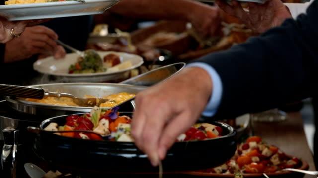 vidéos et rushes de gens obtenir de la nourriture du buffet ouvert - banquet
