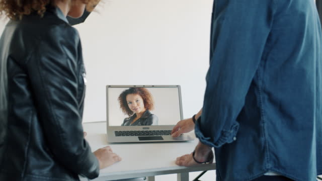 People girl and guy watching photos on laptop screen in photography studio