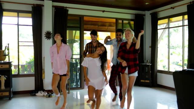 Gens heureux dansant à marcher dans l'appartement Studio moderne, les jeunes hommes et les femmes au groupe d'amis joyeux attache s'amuser - Vidéo