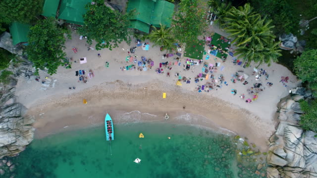 People having a party on a beautiful beach 4k. Cinematic aerial footage. People having a party on a beautiful beach. Blue azure water, Green dense jungle, Bungalows. happy life. Drone footage. beach party stock videos & royalty-free footage
