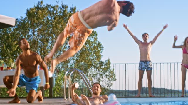 slo mo ds människor att ha kul på en poolparty i solnedgången medan hejar för sin vän som gör en back flip i vattnet - kille hoppar bildbanksvideor och videomaterial från bakom kulisserna