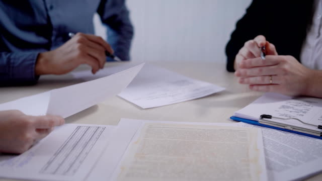 people in an office are discussing a conditions of contract, holding papers in hands, looking and reading - деловая встреча стоковые видео и кадры b-roll