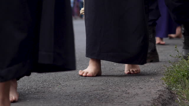 persone in abiti neri che camminano a piedi nudi su una strada asfaltata - anfibio video stock e b–roll