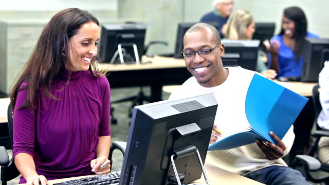 People in computer lab working together on project video