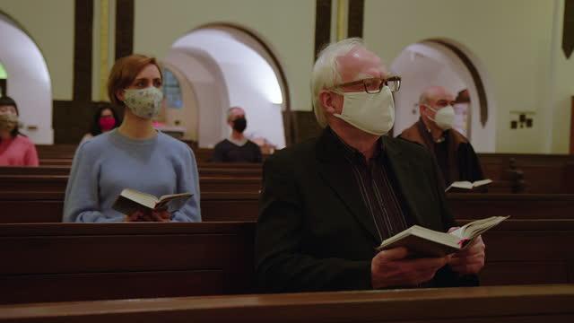 persone in maschere facciali durante la messa religiosa in chiesa - chiesa video stock e b–roll