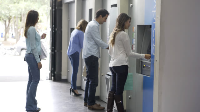 People in line waiting to withdraw money from ATM