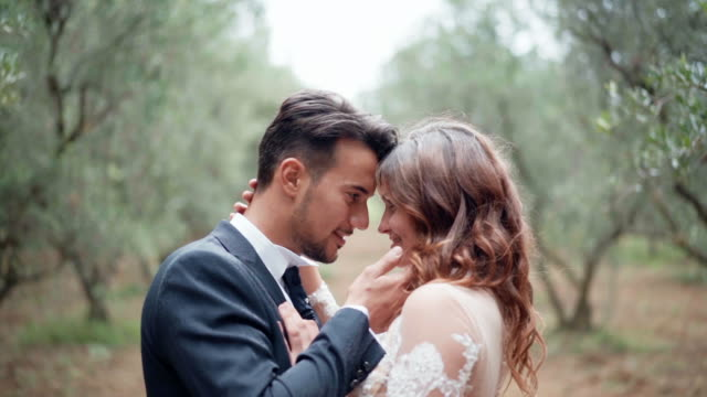 people in love looking at each other eyes and smiling, married couple enjoying the presence of each other in amazing green park, wedding ceremony celebration and different poses for video and photos. romantic emotions of young couple - young couple wedding friends video stock e b–roll