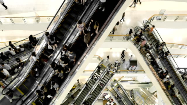 people in motion in escalators at shopping mall - escalator video stock e b–roll
