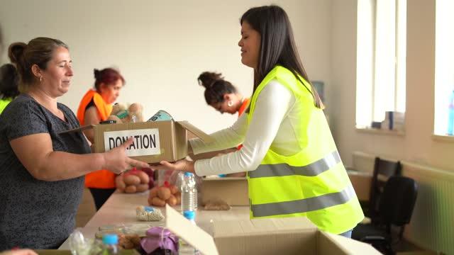 vídeos y material grabado en eventos de stock de las personas necesitadas de recibir una caja de donación de alimentos de un voluntario - food drive