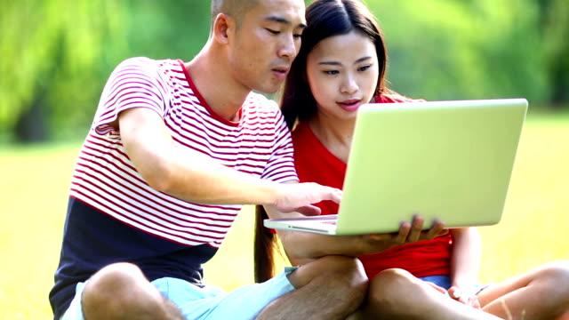People in park using laptop. video