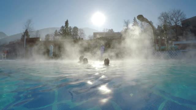 눈와 물으로 겨울 동안 열 스파 수영장의 자연 열 바다에 사람들이 sun evaporations 백라이트 증기 - 스파 온천 스톡 비디오 및 b-롤 화면