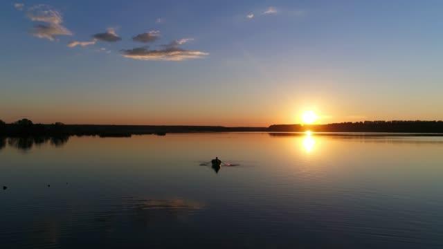 vídeos de stock, filmes e b-roll de pessoas no barco de remo. pôr do sol em um lago ou rio - drone footage - remo atividade física