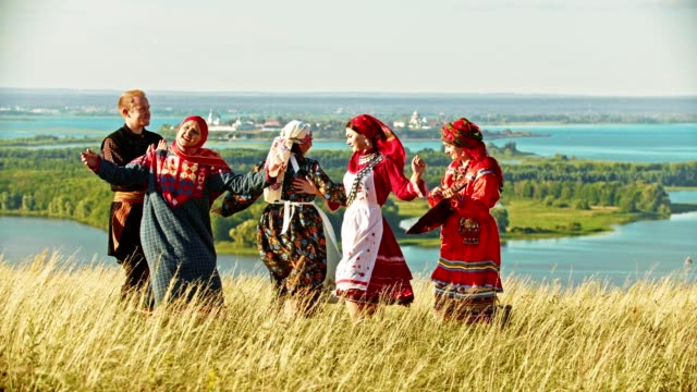 people in traditional russian clothes dancing on the field by the music from balalaika. - славянская культура стоковые видео и кадры b-roll