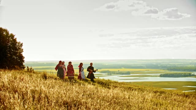 people in traditional russian clothes walking on the rye field - playing balalaika. - славянская культура стоковые видео и кадры b-roll