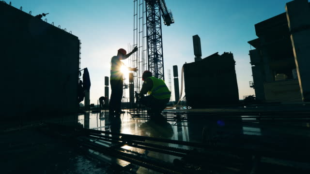 People in uniform work at a construction site. People in uniform work at a construction site. 4K construction equipment stock videos & royalty-free footage